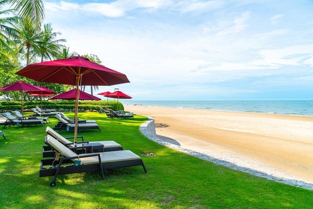 Шезлонг и зонтик на фоне океана море пляж