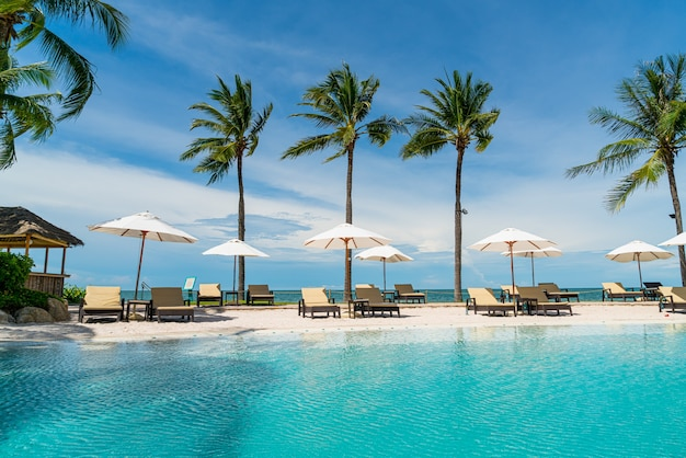 Beach chair around swimming pool in hotel resort with sea beach - holiday and vacation concept