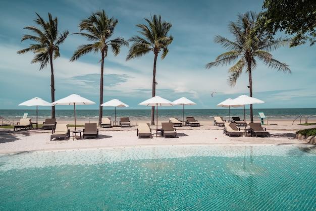 휴가 및 휴가 개념-바다 해변 배경으로 호텔 리조트 수영장 주변 비치 의자