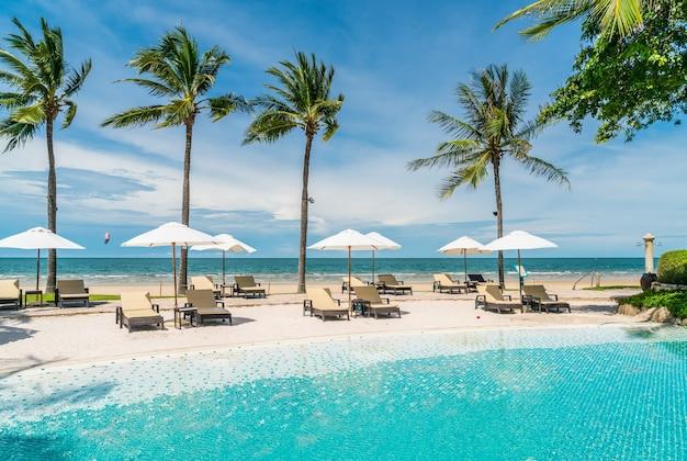 바다 해변이있는 호텔 리조트 수영장 주변의 해변 의자. 휴가 및 휴가 개념