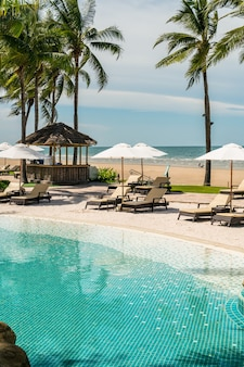 海のビーチとホテルリゾートのスイミングプールの周りのビーチチェア-休日と休暇のコンセプト