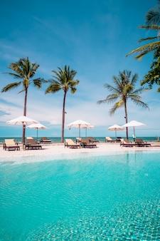 海のビーチとホテルリゾートのプールの周りのビーチチェア
