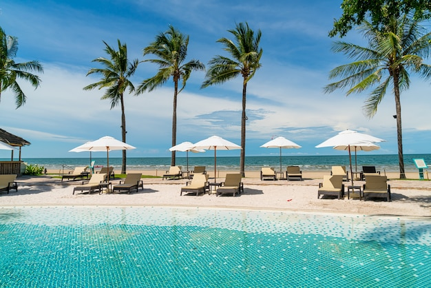 Шезлонг вокруг бассейна в курортном отеле с морским пляжем