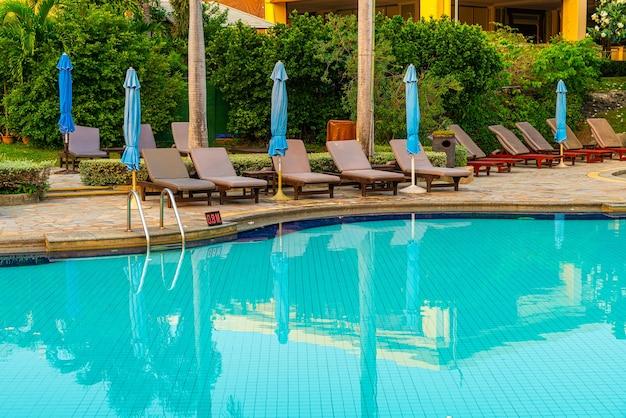 일몰 시간에 수영장 주변에 우산이있는 해변 의자 또는 수영장 침대