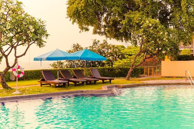 일몰과 바다 테이블이있는 수영장 주변에 우산이있는 해변 의자 또는 수영장 침대