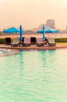 Шезлонг или кровать у бассейна с зонтиком вокруг бассейна с закатом и морем