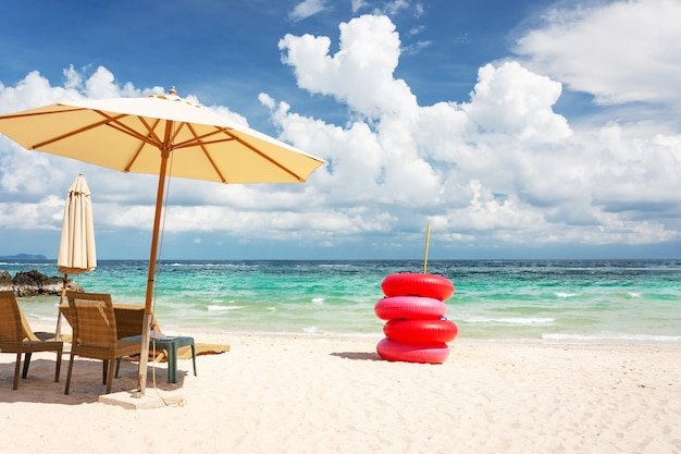 Beach chair, umbrella and red life buoy on the beach and the bright green sea, on a good d