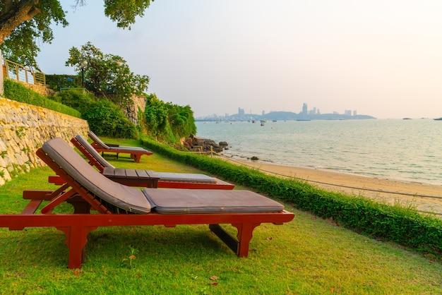 Шезлонг на фоне моря на пляже во время заката в паттайе, таиланд