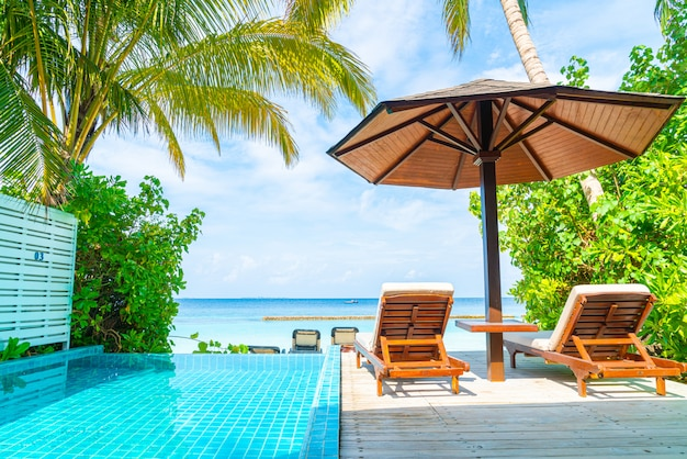 Beach chair with swimming pool and sea background in maldives