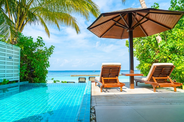 Beach chair with swimming pool and sea in maldives