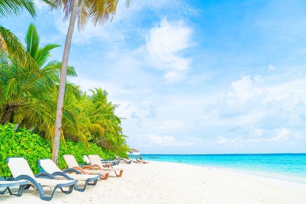 Шезлонг с тропическим островом курортного отеля на мальдивах и морским фоном