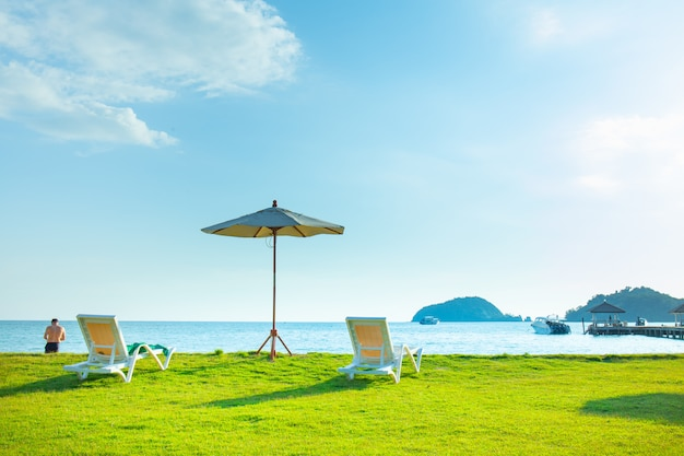 Beach chairs and beach umbrellas are on the lawn at the beach.