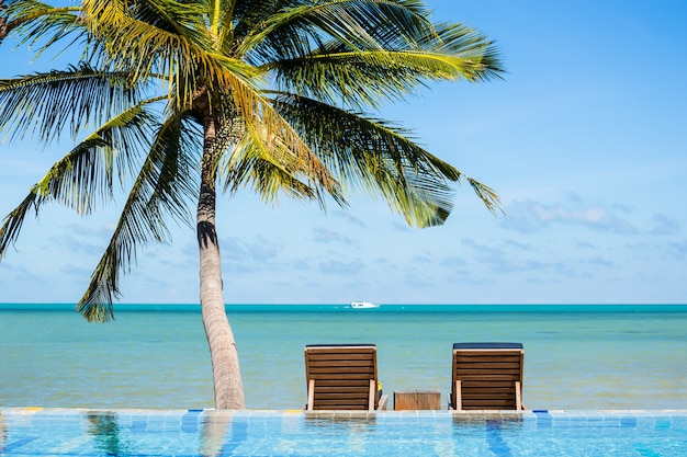 Beach chairs under coconut palm near the sea vacation concept.