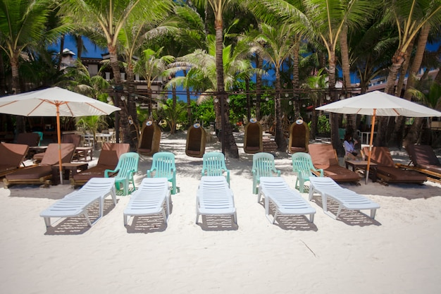 Beach chairs in exotic resort on perfect white sandy beach