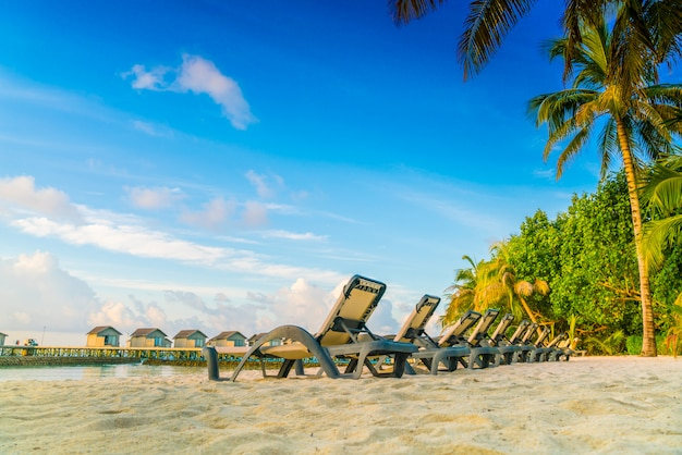 Beach chairs in maldives island with water villas at the sunrise time .