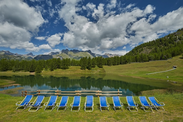 Beach chairs near the lake and hills covered in greenery
