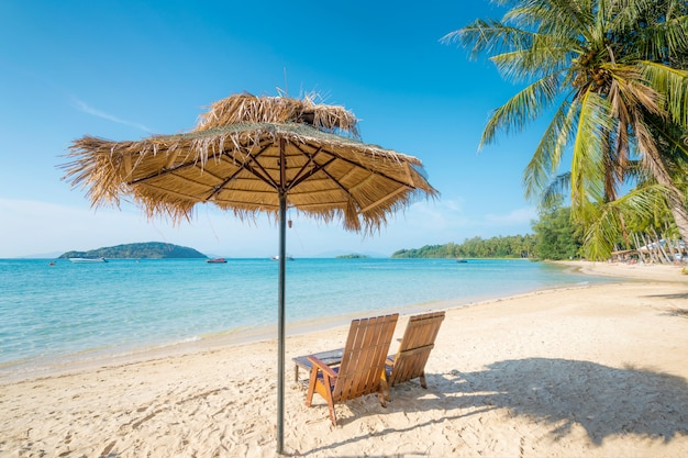Beach chairs and umbrella on summer island with clear water sea and wave with speed boat in phuket, thailand. summer, travel, vacation and holiday concept.