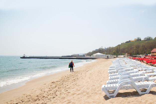 Beach chairs on white sand beach in odessa, ukraine. black sea