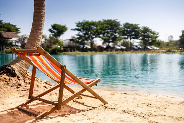 Beach chairs on the white sand beach with cloudy blue sky and sun. tropical holiday banner.