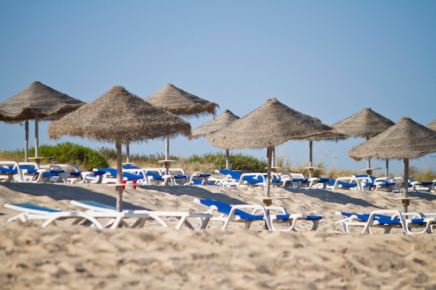 Beach chairs with straw umbrellas