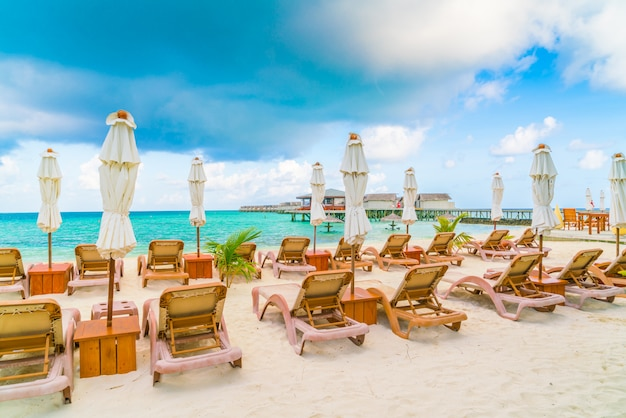 Beach chairs with umbrella at maldives island, white sandy beach and sea .