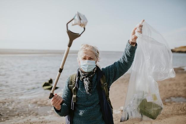 Волонтер-уборщик пляжа несет мешок для мусора для экологической кампании