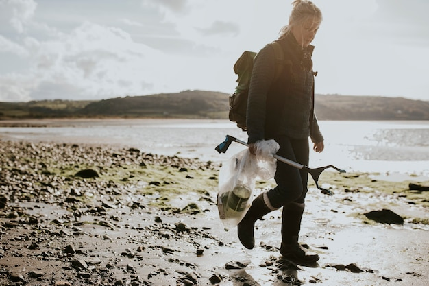 環境キャンペーンのためにゴミ袋を運ぶビーチクリーンアップボランティア