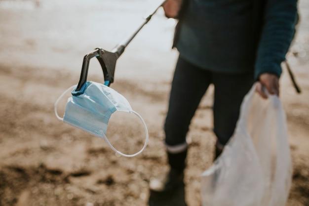Волонтер-уборщик пляжа берет маску для лица для кампании по защите окружающей среды