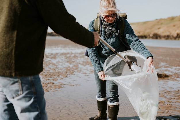Beach cleanup volunteers picking up trash for environment campaign