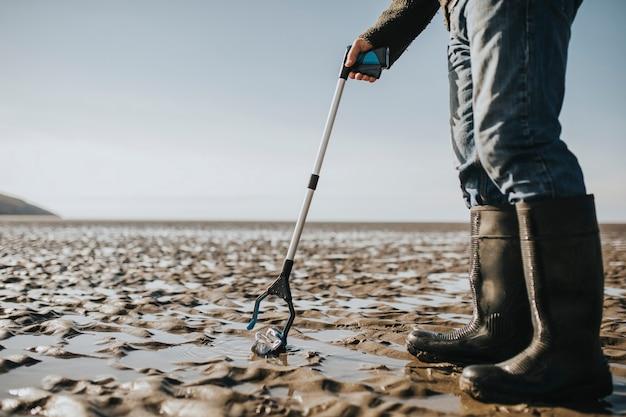 環境キャンペーンのためにゴミを拾うビーチクリーンアップボランティア