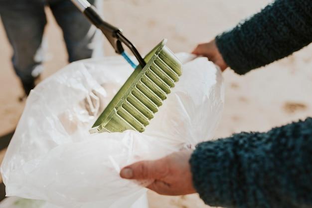 환경 캠페인을 위해 쓰레기를 줍는 해변 청소 자원 봉사자