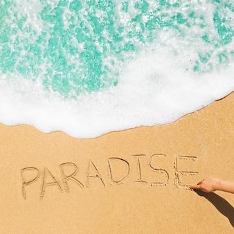 Concetto della spiaggia con il paradiso scritto in sabbia