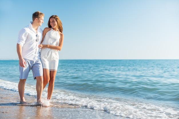 Пляжная пара, идущая на романтическое путешествие, медовый месяц, каникулы, летние каникулы, романтика.