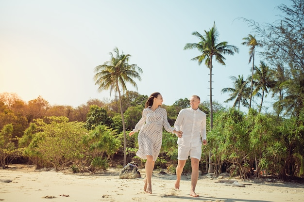 Beach couple walking on romantic travel honeymoon vacation summer holidays romance. young happy lovers, woman and  man holding hands embracing outdoors. tropical forest on the background