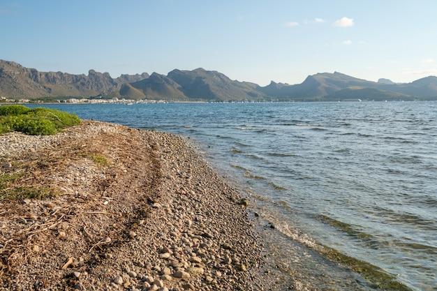 Галечный пляж и горный хребет, расположенный недалеко от чистого волнистого моря солнечным утром.