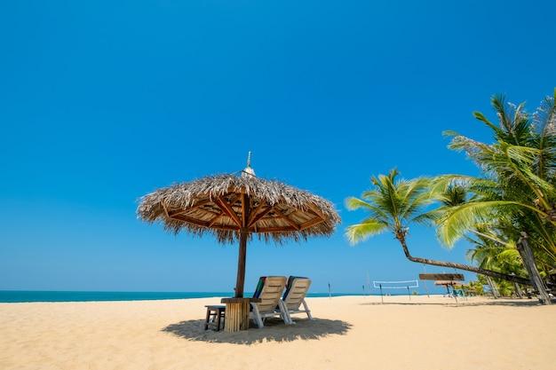 熱帯のビーチの荒野の砂の上にビーチデッキチェアと傘