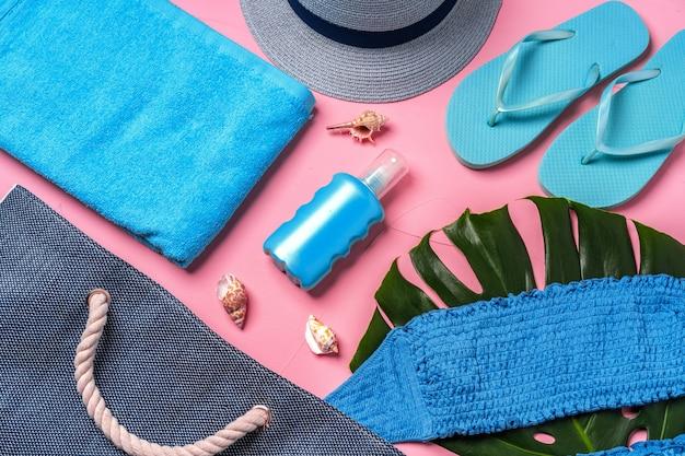 ピンクの背景にビーチの必需品と青いビーチバッグ