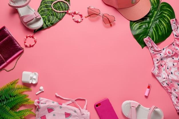 ビーチファッションコンセプトフラットレイガールズアクセサリーとピンクの背景に緑の葉を持つ服...