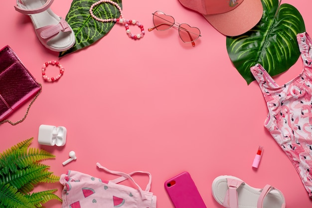 Beach fashion concept flat lay girls accessories and clothes with green leaves on pink background fl...