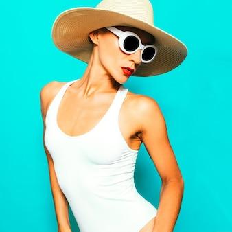 ビーチファッション。ビーチアクセサリーの官能的な女性。帽子とサングラス。白のスタイリッシュな水着