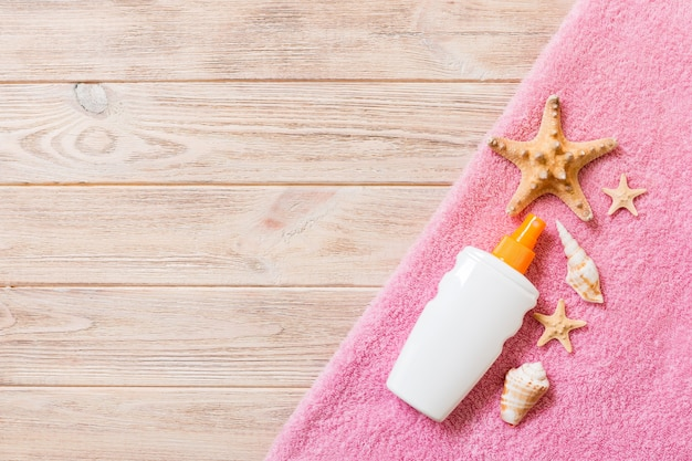 Beach flat lay accessories with copy space. pink towel, starfish and a bottle of sunblock on wooden background. summer holiday concept.