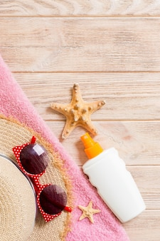 Beach flat lay accessories with copy space. striped blue and white towel, seashells, sunglasses, staw sunhat and a bottle of sunblock on wooden background. summer holiday concept.