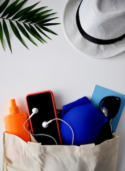 Beach flat lay traveler accessories, palm leaf, phone, sunscreen, hat, sunglasses, headphones