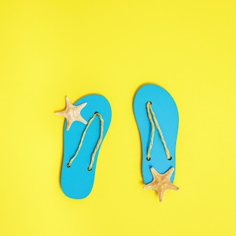 Beach flip-flops and small starfishes on bright yellow paper