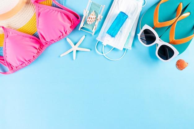 ビーチ帽子、ビキニ、サングラス、医療マスク、明るい青の背景に手の消毒剤。夏。