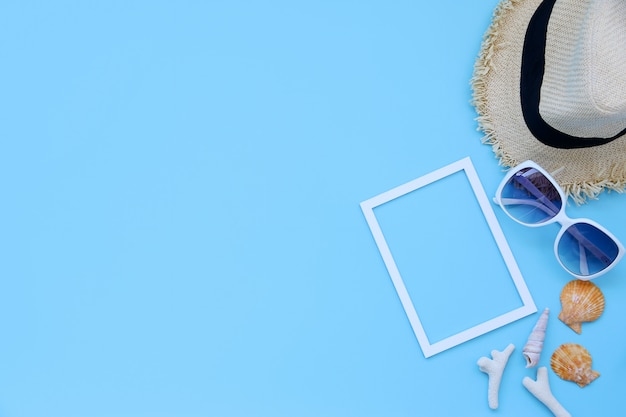 Beach hat,glasses,picture frame and shellson blue background in the summer asia,copy space,top view,minimal style