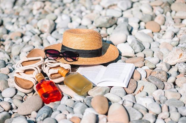 日焼け止めと小石のビーチで靴を開いた本のビーチハット