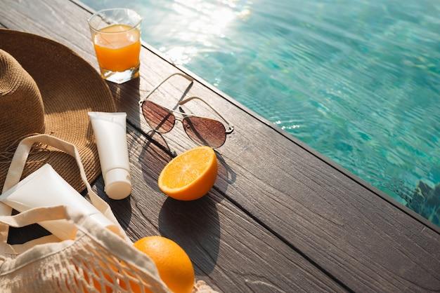 スイミングプールの近くのビーチハット、オレンジジュース、サングラス