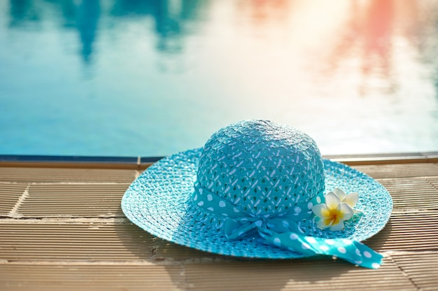 Beach hat next to the summer pool in the setting sun