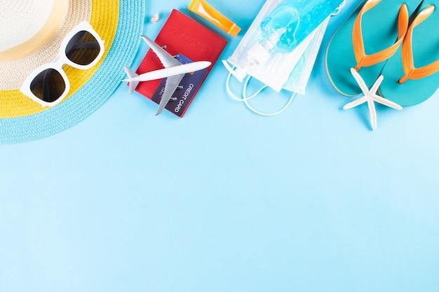 ビーチ帽子、サングラス、防護マスク、手の消毒剤、明るい青の背景のパスポート。夏。